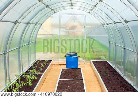 Small Plastic  Greenhouse In Backyard In Garden. Planting Seedlings In A Polycarbonate Hothouse On B