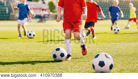 Sporty Children On Football Summer Camp. Kids Practicing Football On Grass Field. Football Soccer Ch