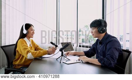 Asian Woman Radio Hosts Gesturing To Microphone While Interviewing A Man Guest In Radio Station Duri