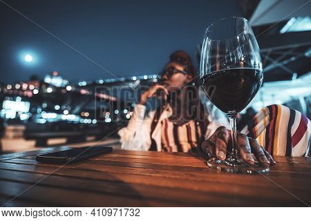 A Night Shot Of A Young Black Tourist Female With A Glass Of Wine In An Outdoor Cafe Pensively Looki