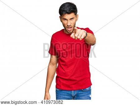 Young handsome man wearing casual red tshirt pointing displeased and frustrated to the camera, angry and furious with you