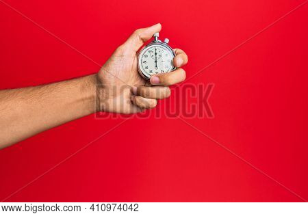 Hand of young hispanic man using stopwatch over isolated red background.