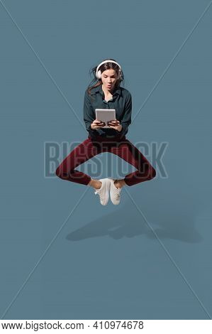 Jumping High With Tablet And Headphones. High Angle View Of Young Woman On Blue Background. Human Em
