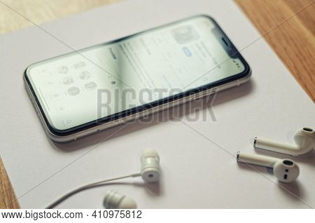 Minsk, Belarus, March 2, 2021: Various Types Of Earphones And Earbuds, Smartphone With Blurred Clubh