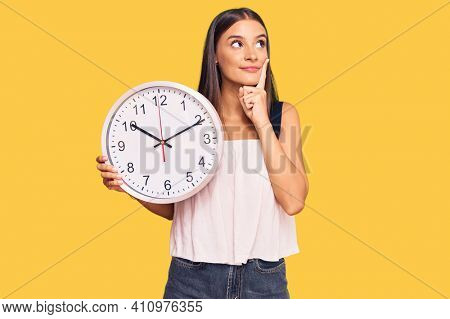 Young hispanic woman holding big clock serious face thinking about question with hand on chin, thoughtful about confusing idea