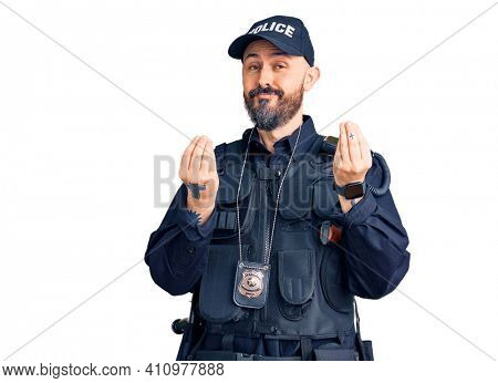 Young handsome man wearing police uniform doing money gesture with hands, asking for salary payment, millionaire business