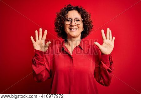 Middle age beautiful curly hair woman wearing casual shirt and glasses over red background showing and pointing up with fingers number ten while smiling confident and happy.