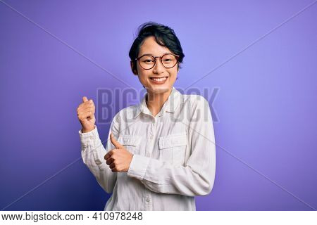 Young beautiful asian girl wearing casual shirt and glasses standing over purple background Pointing to the back behind with hand and thumbs up, smiling confident