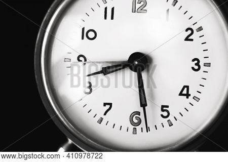 A Black-and-white Image Of The Dial Of An Old Clock That Shows Half Past Eight In The Morning. The C