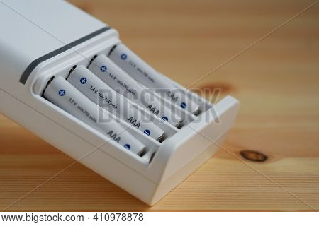 Selective Focus Rechargeable Aaa Battery In A White Charger On Wooden Background.