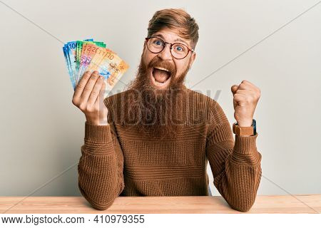Young irish redhead man holding swiss franc banknotes sitting on the table screaming proud, celebrating victory and success very excited with raised arm