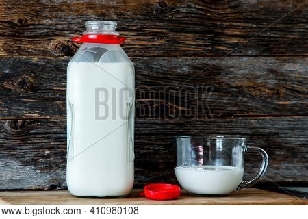 Bottle with organic milk  in kitchen with rustic looking wooden background