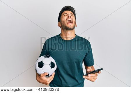 Young handsome man holding football ball looking at smartphone bet app angry and mad screaming frustrated and furious, shouting with anger looking up.