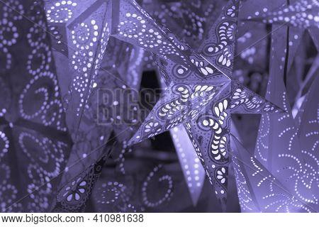 Colorful Purple Xmas Lantern Stars At Christmas Market Season. Beautiful Shiny Star Mood Lamp In Mer