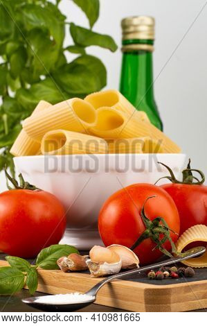 In The Foreground Is A Blurred Image Of Pepper, Cloves Of Garlic, A Spoon With Salt, A Tomato, In Th