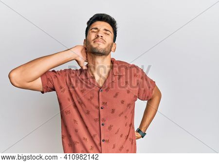 Young handsome man wearing casual summer clothes suffering of neck ache injury, touching neck with hand, muscular pain