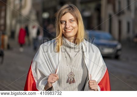 Street Portrait Of A Cheerful Refugee With A Belarusian Flag On Her Shoulders. 25-30-year-old Woman