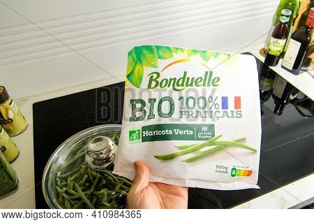 Paris, France - Mar 2, 2021: Pov Male Hand Holding Above Induction Plate The Package Of Bonduelle Bi