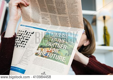 Paris, France - Mar 2, 2021: Business Woman Reading Financial Times Newspaper With Advertising Of Mi