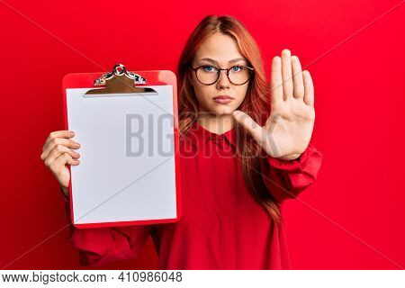 Young redhead woman holding clipboard with blank space with open hand doing stop sign with serious and confident expression, defense gesture
