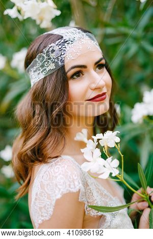 The Bride Stands By A Blooming White Oleander And Holds A Sprig Of Oleander In Her Hands