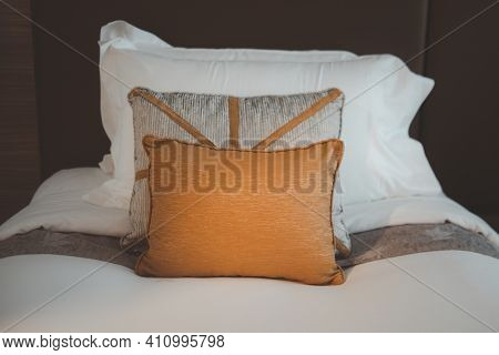 Bed With Clean White Pillows And Scatter Cushion In Hotel Room. Close-up.