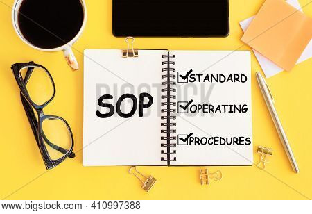 Sop - Standard Operating Procedure, Text On Notepad And Office Accessories On Yellow Desk.