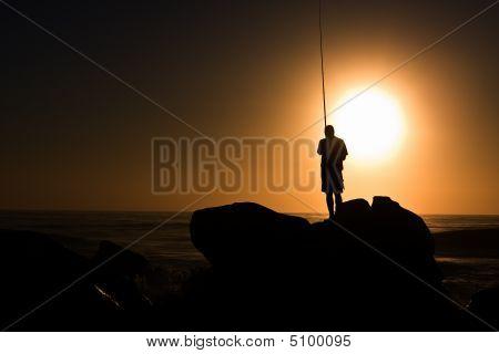 Lone Fisherman On Rock