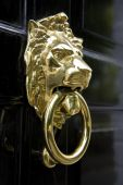 lion-head with the ring made of metal on front of the wooden door in UK poster