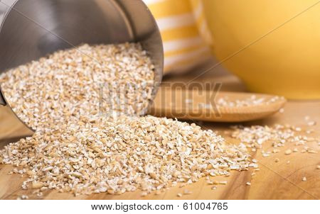 Healthy steelcut whole oats spilling out of a measuring cup