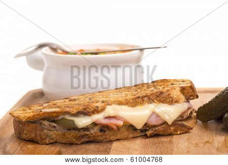 Delicious Cuban panini made with ham, pork and swiss cheese served with a vegetable soup, pickles