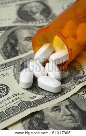Bottle of pills spilling onto one hundred dollar bills