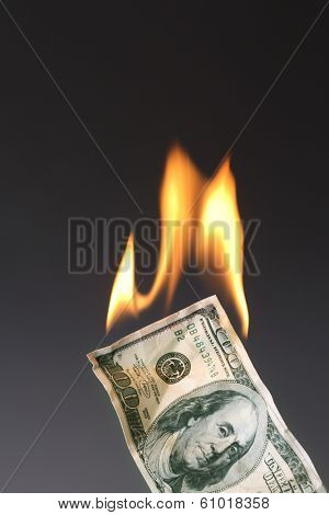 One hundred dollar bill on fire with black background