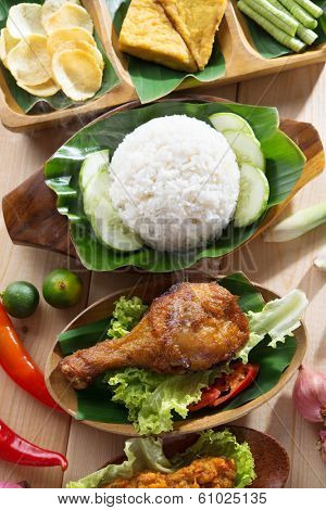 Popular Indonesian local food nasi ayam penyet, indonesian fried chicken rice. Fresh hot with steam smoke.