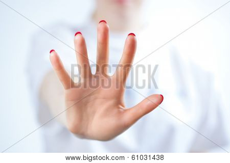 Young woman showing palm handsign.