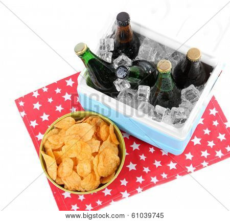 Ice chest full of drinks in bottles on color napkin, isolated on white