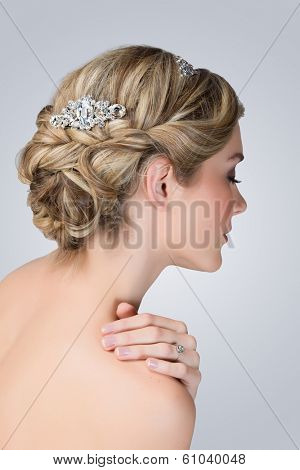 Bridal hairstyle with vintage style hair accessories. Blond Bride. View from the back  poster