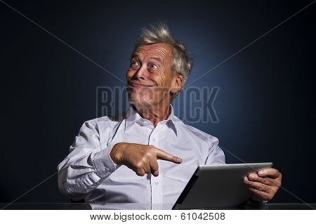 Senior businessman grinning with a look of fatuous self-satisfaction and pointing to his tablet computer with his finger as though indicating a great personal achievement comic studio portrait poster