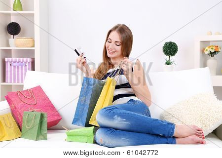 Young woman sitting with  on sofa and holding credit card in her hand, at home