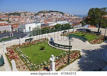 Lisbon, Portugal - May 26, 2013: Miradouro de Sao Pedro de Alcantara (Belvedere) in the Bairro Alto District and a view of the Baixa District and the Sao Jorge Castle of Lisbon, Portugal -