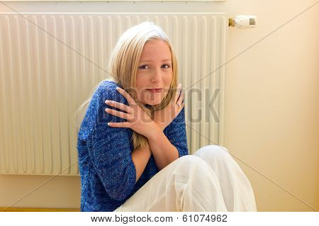 a young woman sits in front of a radiator in winter. room temperature is too low. poster