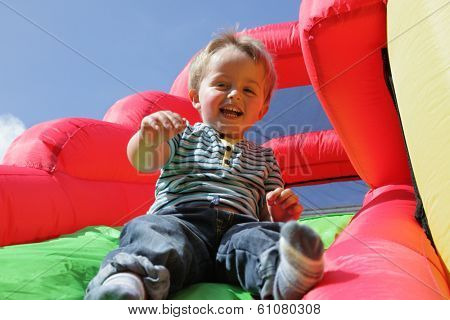 2 year old boy jumping down the slide on an inflatable bouncy castle