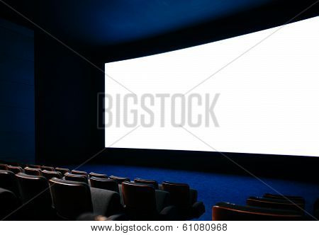Cinema auditorium with large screen and empty seats poster
