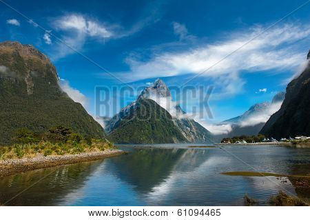 Famous Mitre Peak rising from the Milford Sound fiord and reflecting in water. Fiordland national park, New Zealand poster