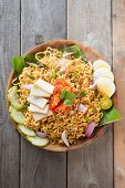 Malaysian style maggi goreng mamak  or spicy dried curry instant noodles.  Asian cuisine, ready to serve on wooden dining table setting. Fresh hot with steamed smoke. poster