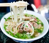 Bowl of Vietnamese pho noodle soup with rare beef tendon tripe and brisket served with onions scallions and cilantro. poster