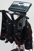 Training suit hanging on Modern Electro Muscular Stimulation EMS machine  poster