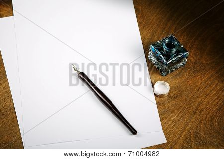 Ink Pot And Quill With Sheets Of Paper On A Table