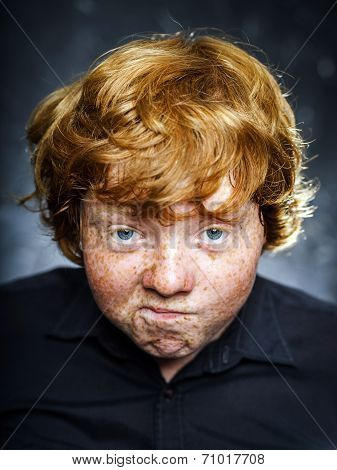 Fat freckled boy studio portrait in dark background poster