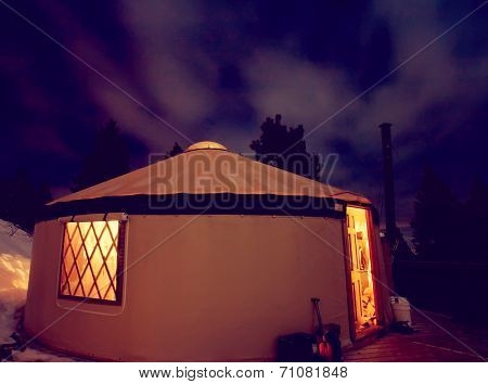 a yurt in the snowy mountains at night toned with a retro vintage instagram filter effect